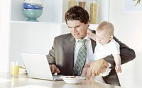 Business man holding son 18-24months, using laptop at table