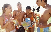 Two young couples in swimwear eating crisps outdoors