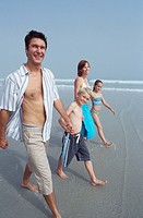 Family including boy and girl 9-11 walking on beach, portrait