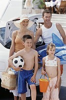 Parents with daughter 8-9 years and son 12-13 years standing with beach toys next to car
