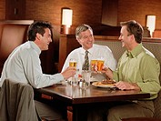 Three businessmen toasting with beer in restaurant