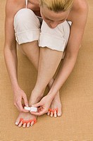 Woman applying nail polish to toes