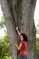 Young woman stands beside trunk of large tree, Munson Park, Winnipeg, Canada