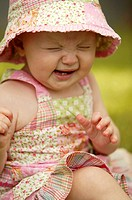 Toddler wearing sunhat with sneezing expression, Saskatchewan, Cnada