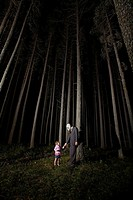 Man in Gas Mask and suit with little girl stand beside eerie trees at night, Cypress Hills, Saskatchewan