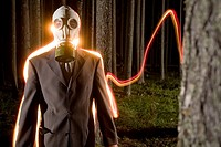 Light stream behind man wearing gas mask in nighttime forest