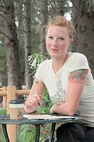 Woman seated at outdoor restaurant, corn-based compostable coffee cup on table, Wasagaming, Riding Mountain National Park, Manitoba, Canada