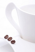 Close_up of cup and saucer with coffee beans