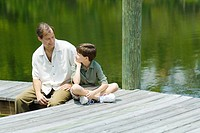 Father and son sitting on dock, smiling at each other