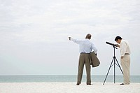 Two businessmen standing at the beach, one looking through telescope, the other pointing