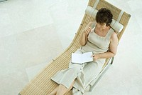 Woman sitting on lounge chair writing in diary, high angle view