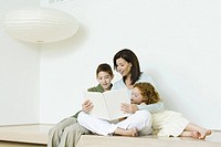 Mother reading book to boy and girl