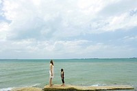 Mother and daughter standing by ocean, looking toward horizon, full length