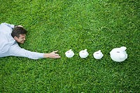 Man lying on grass, reaching for line of piggy banks