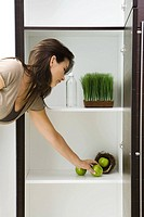 Woman reaching for apple in pantry containing apples in nest, tray of wheat grass and bottle of water