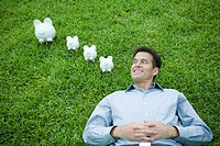 Man lying on grass, next to piggy banks, smiling