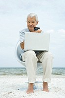 Senior man making credit card purchase online, holding up credit card, sitting in chair on beach
