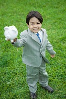 Little boy wearing full suit, holding up piggy bank, smiling at camera, full length