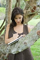 Woman leaning against tree branch, writing in book, looking down