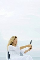 Woman photographing self with cell phone, sticking out tongue, eyes closed