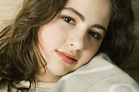 Teen girl, resting cheek on blanket, portrait