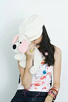 Teenage girl hiding face with stuffed toy, laughing