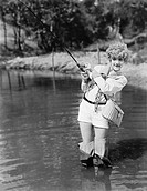 Young woman wearing waders holding a fishing rod All persons depicted are not longer living and no estate exists Supplier warranties that there will b...