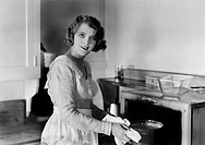 Young woman in her kitchen putting a pot into the oven All persons depicted are not longer living and no estate exists Supplier warranties that there ...