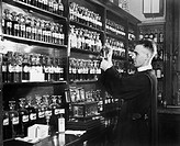 Man in a pharmacy mixing medicine All persons depicted are not longer living and no estate exists Supplier warranties that there will be no model rele...