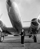 Woman standing under a large aircraft looking up All persons depicted are not longer living and no estate exists Supplier warranties that there will b...