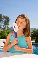 Young girl eating cream with a spatula