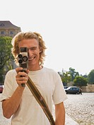 Smiling Young Man Holding Cine Camera