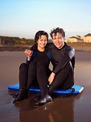 Couple in wetsuits sitting on body board