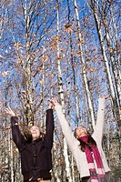 2 young woman throwing leaf in the air