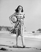 Woman walking on beach carrying ball All persons depicted are not longer living and no estate exists Supplier warranties that there will be no model r...