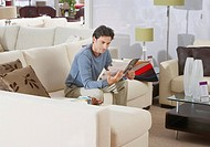 Man sitting on sofa in furniture store