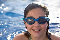 Young girl in pool with swimming goggles on