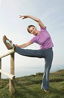 A Woman Stretches on a country fence