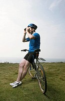 A male cyclist looks through binoculars