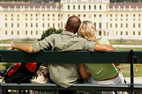 Young Couple Sitting on Bench Looking at Schonbrunn Palace, Vienna, Austria, Europe