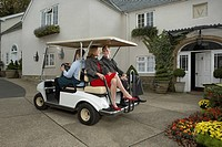 Man driving cart with man and woman