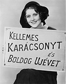 Portrait of woman holding sign written in foreign language All persons depicted are not longer living and no estate exists Supplier warranties that th...