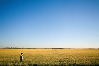 Farmer stands in field of wheat, Saskatchewan, Canada