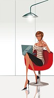 Portrait of a businesswoman sitting on an office chair and using a laptop