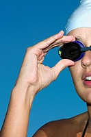 Close-up of a young woman adjusting her swimming goggles