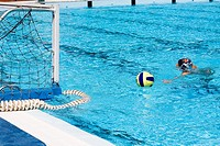 Man playing water polo in a swimming pool