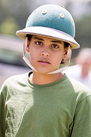 Portrait of a teenage boy wearing a polo helmet