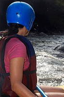 Side profile of a woman rafting in a river