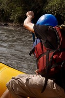 Side profile of a person rafting in a river
