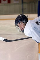 Side profile of an ice hockey player leaning over the railing of an ice rink